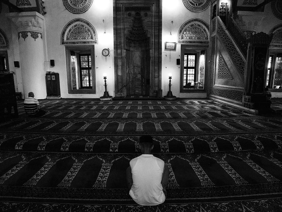 The worshipper faces the mihrab and the distant Ka'ba in prayer.