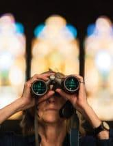 woman looking at stained glass windows through binoculars